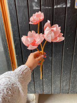 papirblomster af lyserode Magnolia blomster på grene lavet i italiensk crepe papir