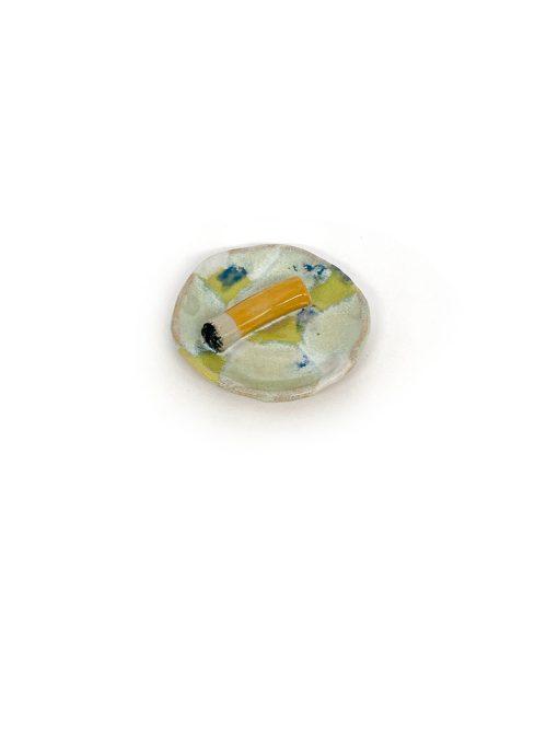 Julie Ebens mini keramik askebæger i lysefarver med et cigaretskod i