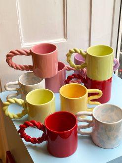 Studio Palu kopper i forskellige farver med snoede hanke